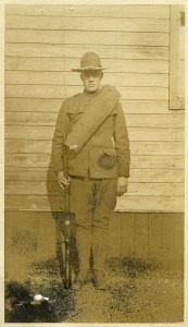 Delbert in uniform, standing at attention with his rifle at his side.