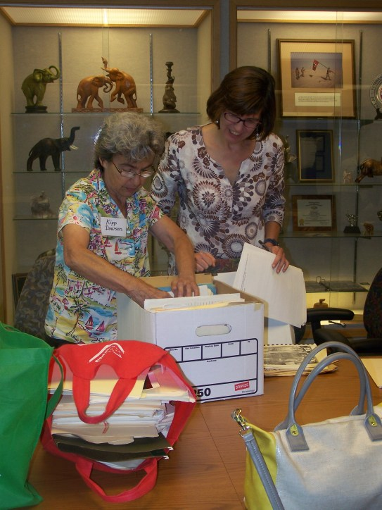Jen Bingham, Collections Archivist, assists Kipp Dawson with donating materials to the Archives.