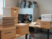 Student assistant Sierra sorts through correspondence, surrounded by boxes-in-waiting.