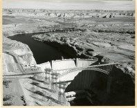 Aerial view of Glen Canyon Dam. Newly built visitors center can be seen on the left end of the dam, October 10, 1967.
