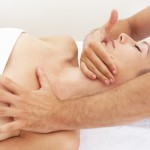 Physiotherapist massaging tight neck muscles and gently stretching to relieve pain