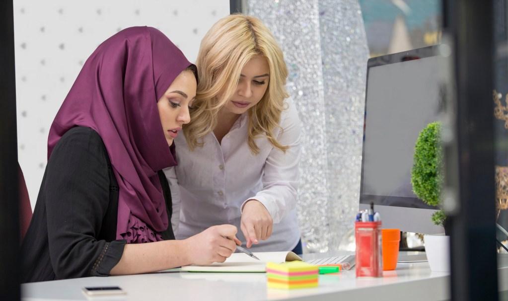 European woman helps asian muslim woman learn English
