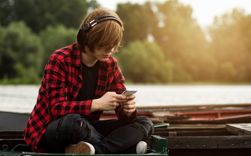 teenage boy listens to music outdoors on a dock