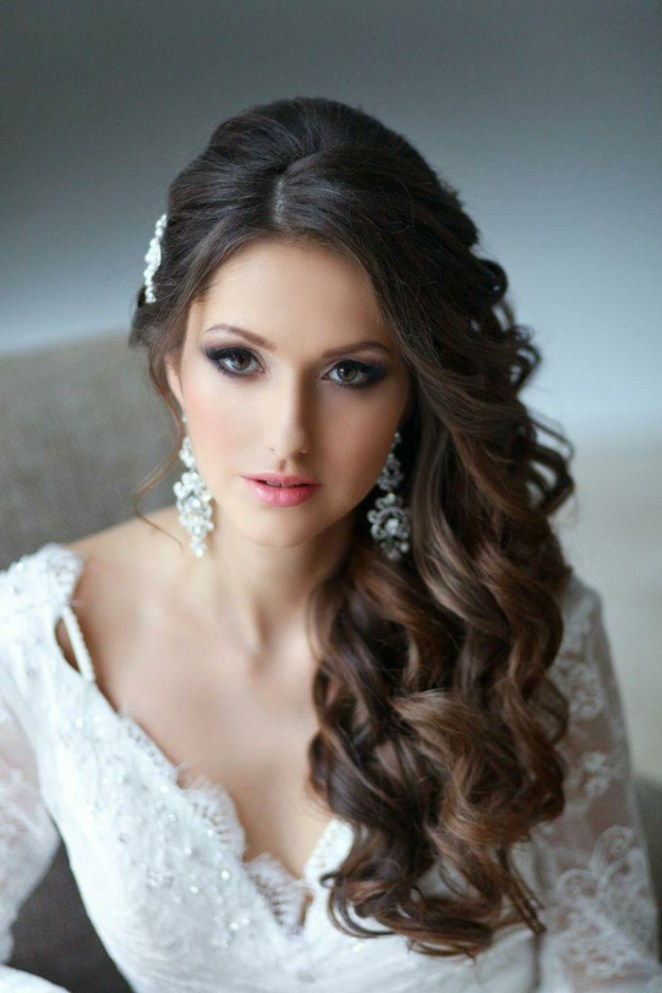 a beautiful bride with curly hair, long earrings, casual curls and hair accessories