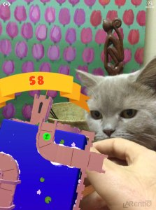 Cat looking at an AR game on Merge Cube