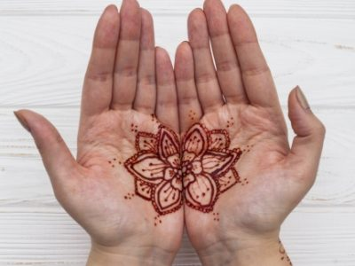 Optimized-female-hands-with-mehndi-on-table