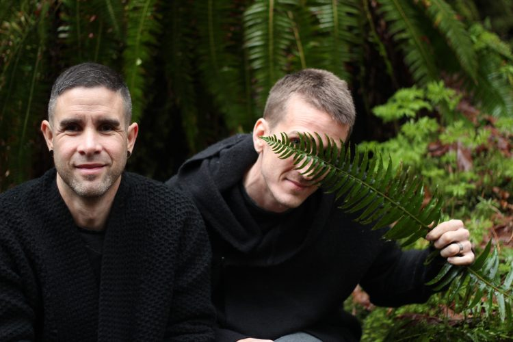 Two men wearing black in the Pacific Coastal Rainforest in BC, one man covering his eyes with a fern frond