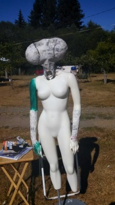 Here she is without the table cloth dress, the head is now fully formed, and from this point on it sat drying in the sun daily while I worked on the rest of the mannequin.  You can see that there is paper mache on the arms too, but the next photo will show more detail.