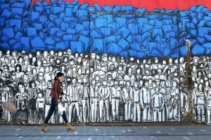 A woman walks past a mural depicting many famous Serbs and the Serbian national flag in Belgrade on April 22, 2016. Serbian Prime Minister Aleksandar Vucic, who is bidding for another four years in power in Sunday's general election, is a former ultra-nationalist and close ally of Slobodan Milosevic remade as a pro-European liberal. In a political transformation viewed by critics as pragmatic rather than ideological, the tall 46-year-old Vucic now leads Serbia's efforts to join the European Union. / AFP / ANDREJ ISAKOVIC        (Photo credit should read ANDREJ ISAKOVIC/AFP/Getty Images)