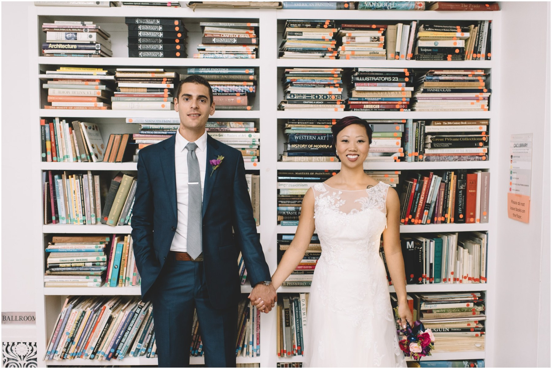 Bride and groom portrait in front of book case