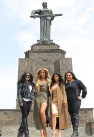 Kim Kardashian poses with Khloe and her cousins at Statue of Armenia as the police keep watch on them