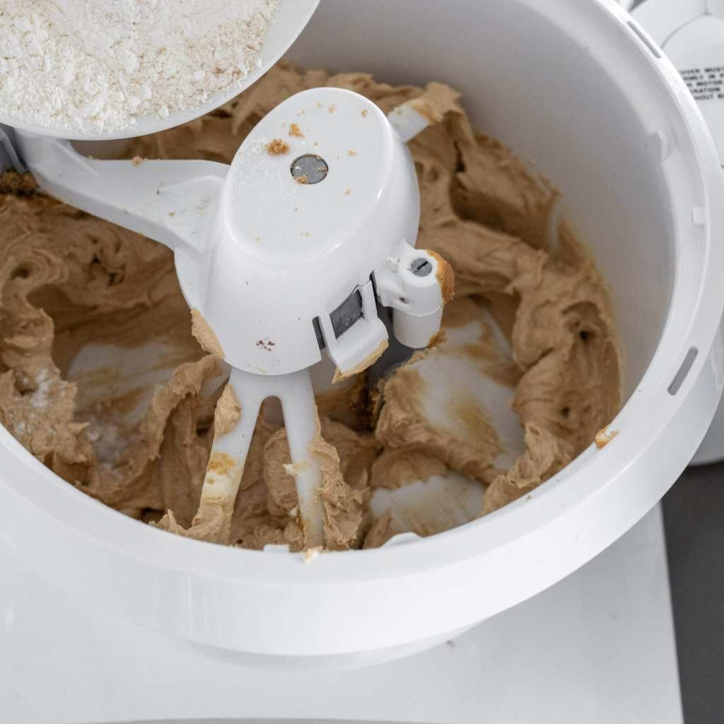 adding flour to peanut butter chocolate chunk cookie dough