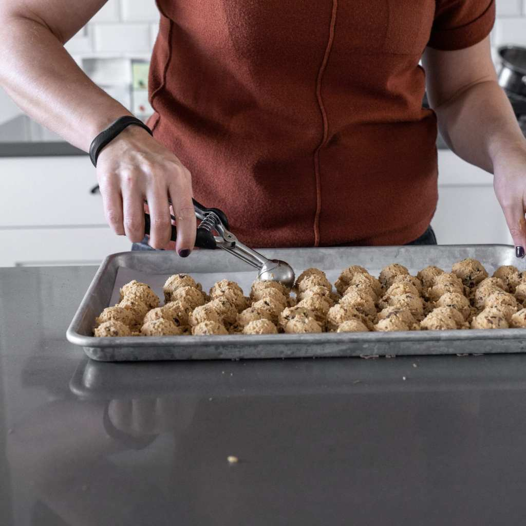 scooping peanut butter chocolate chunk cookies onto parchment lined baking sheet