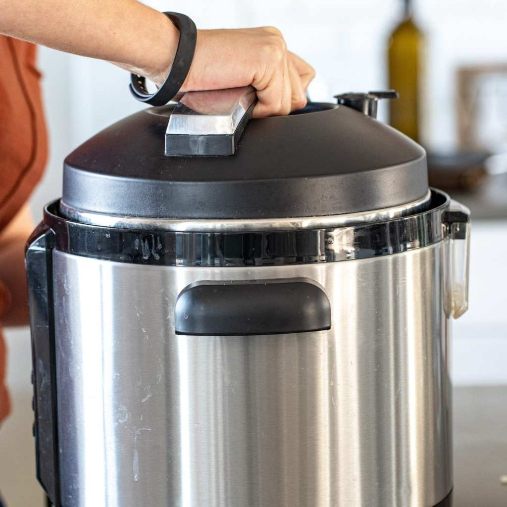 woman sealing the lid on her instant pot.