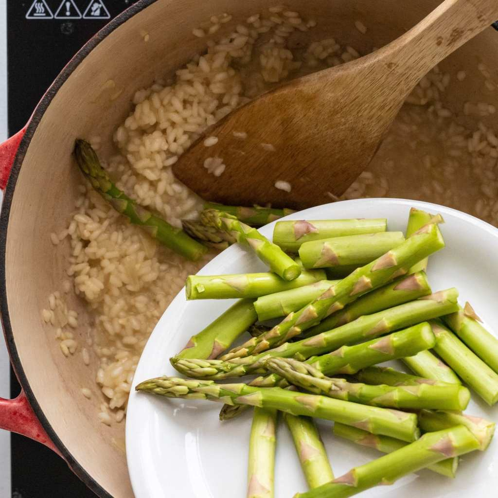 woman adding in asparagus into a pot for risotto