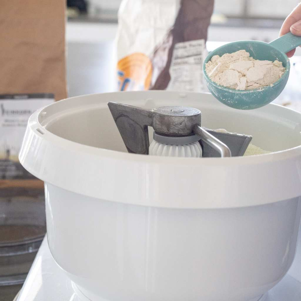 adding einkorn wheat to a bosch stand mixer with measuring cup
