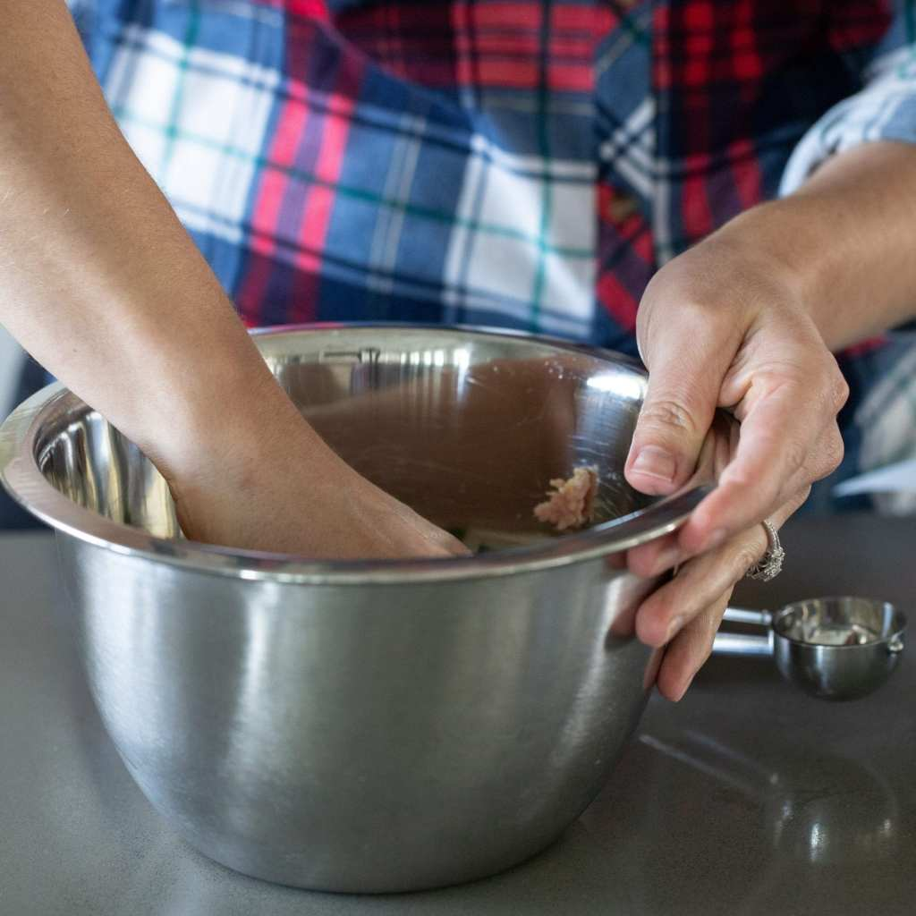 Mixing ground turkey for meatballs in metal bowl