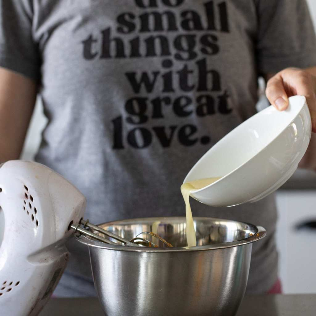 woman pouring melted butter into metal bowl to make pizzelles