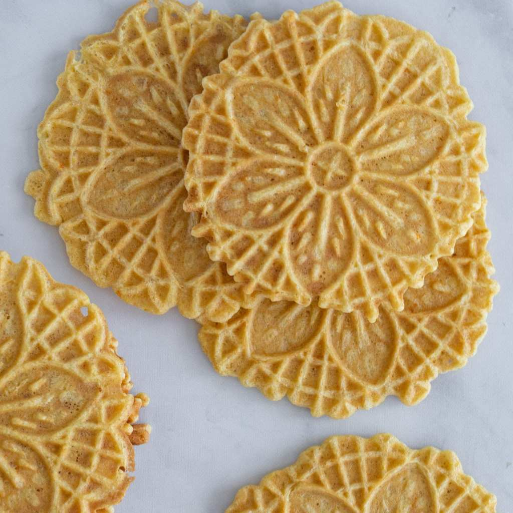multiple pizzelle cookies laid on marble surface