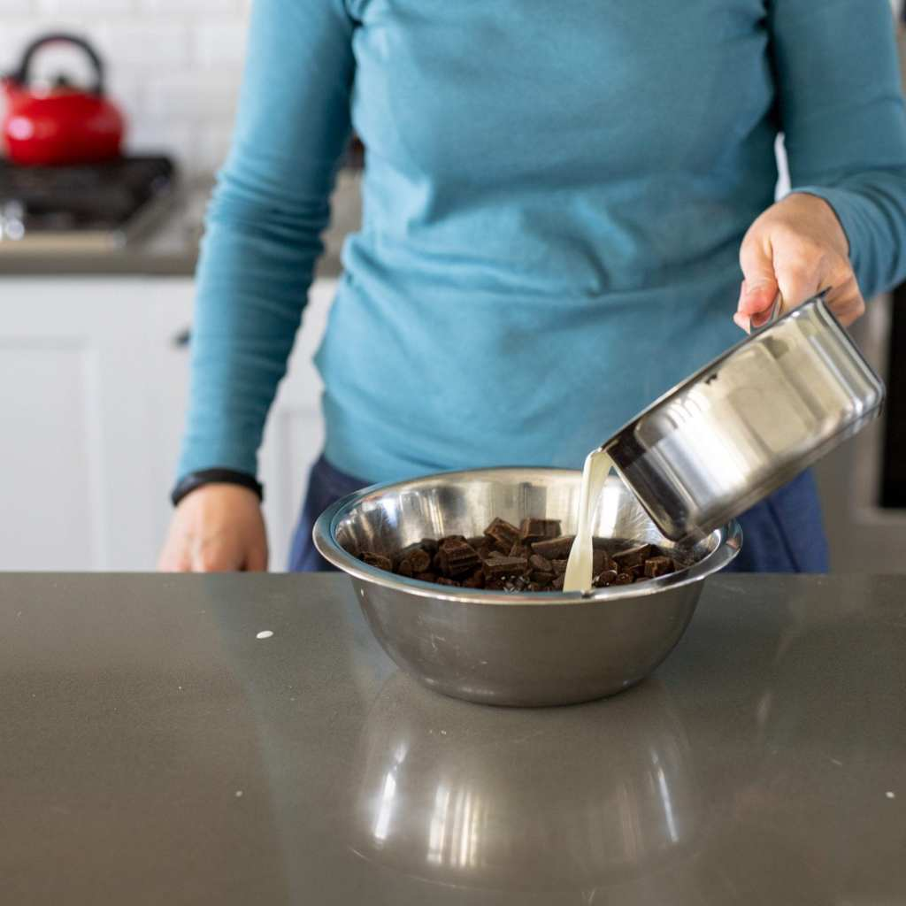 woman pouring heavy cream into small stainless steel pan filled with dark chocolate to make ganache.