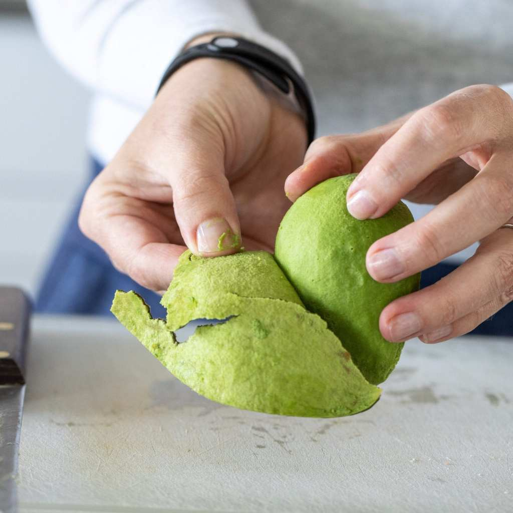 woman peeling the skin off avocado.