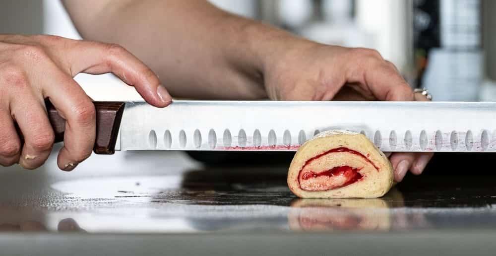 woman slicing raspberry sweet rolls with long sharp knife