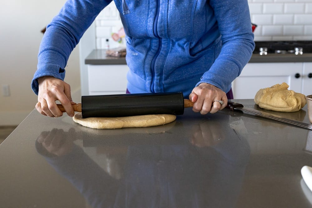 woman rolling whole grain dough on counter top with rolling pin
