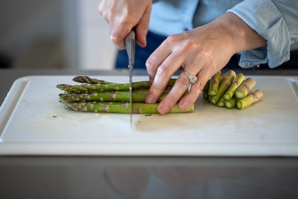 woman cutting asparagus with a chef's knife on a plastic cutting board into chunks for roasting.
