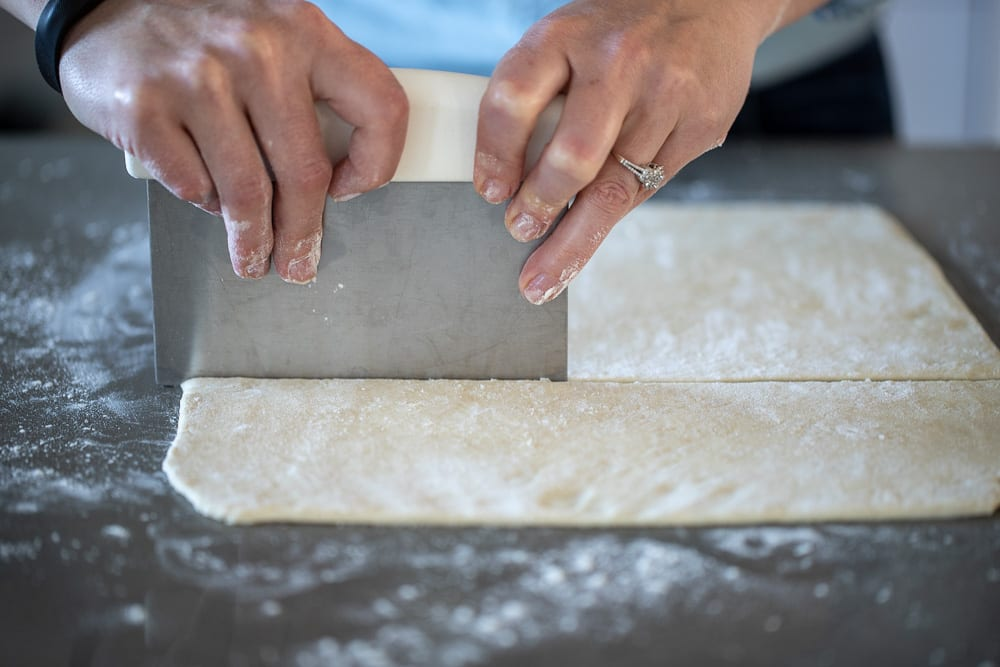 woman cutting pie dough with a bench knife on a lightly floured surface