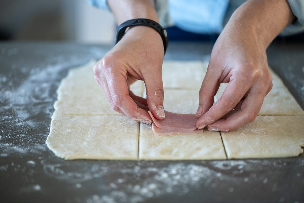woman placing ham slices on pie dough rectangles for ham and cheese pockets