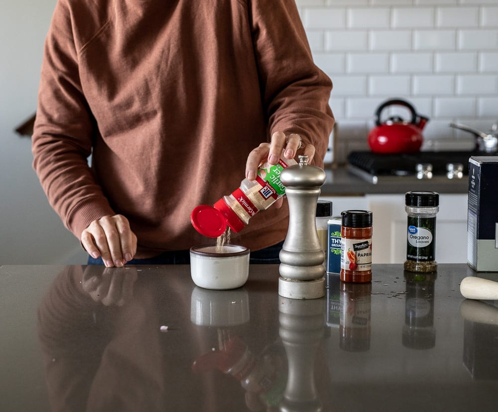 woman pouring garlic powder into small bowl with various dried spice containers on the counter top
