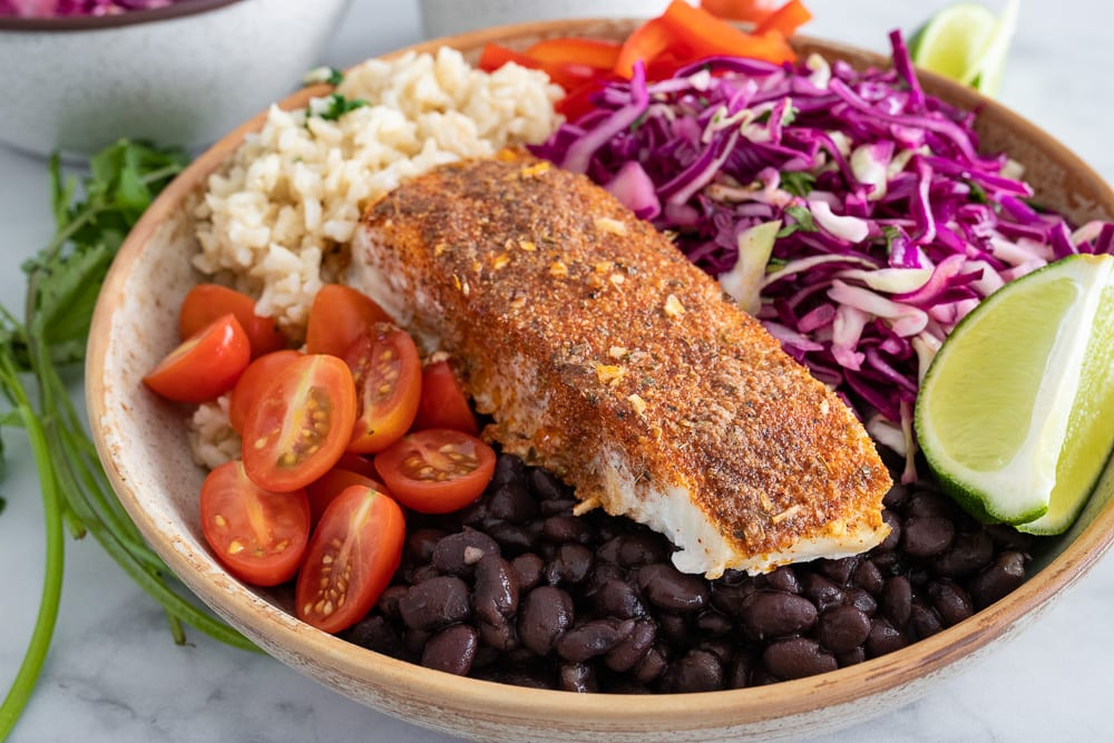 blackened halibut bowl in a ceramic bowl filled with cabbage, tomatoes and black beans