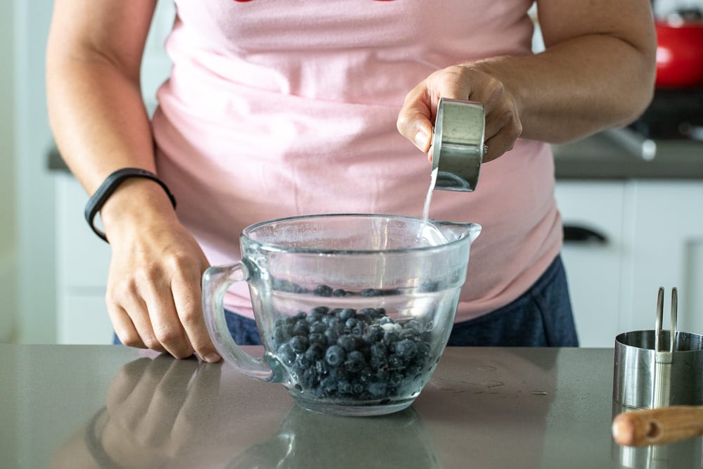 woman pouring sugar over fresh blueberries for blueberry hand pies