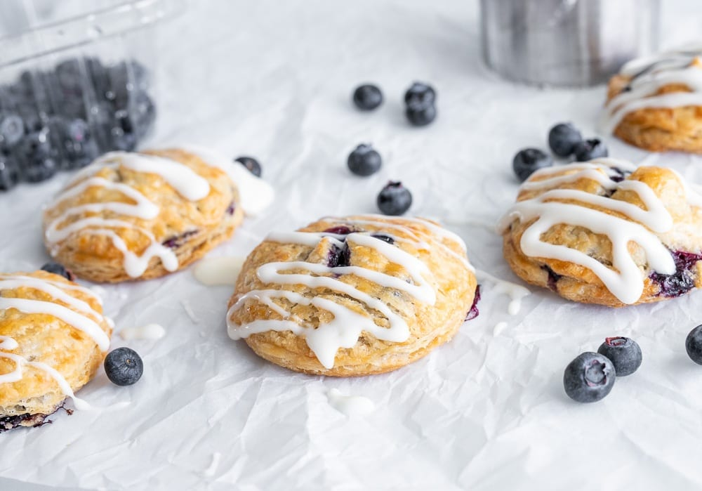 baked blueberry hand pies on crinkled parchment paper, drizzled with cream cheese icing. Blueberries and container are scattered in the background.