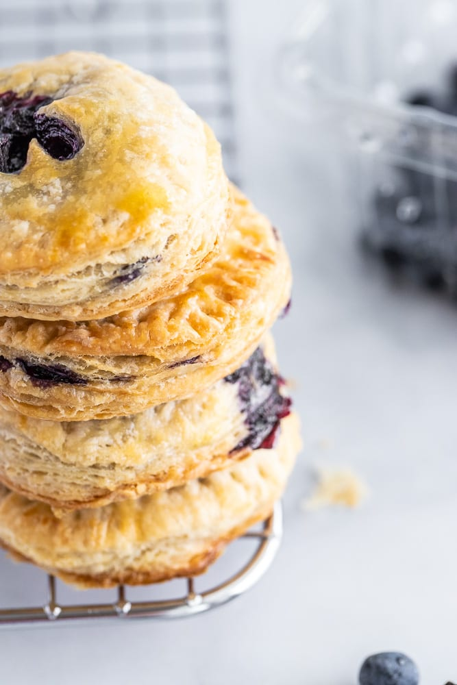 blueberry hand pies stacked on top of each other on a cooling rack