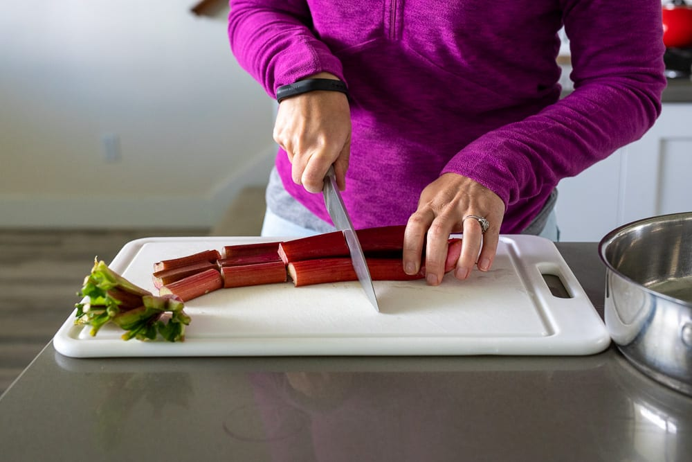 woman cutting up rhubarb on plastic white cutting board with a chef's knife.