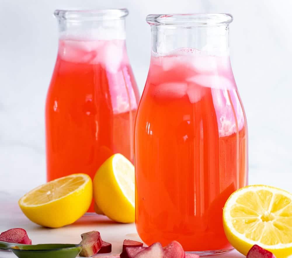 perfect rhubarb lemonade on counter top with cut lemons and diced rhubarb