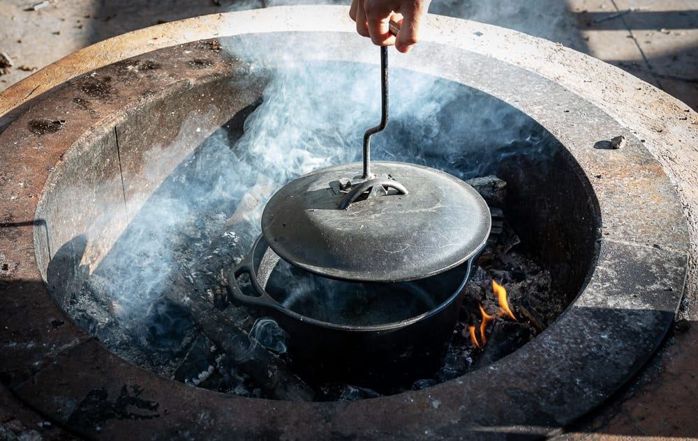 woman removing lid from dutch oven with a lid lifter over a bed of coals in a fire ring