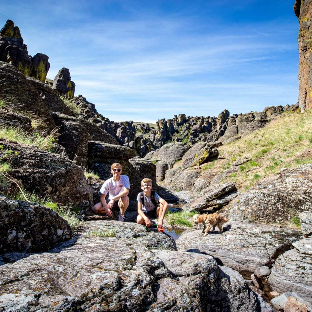 2 boys and a cavapoo hiking near pool in little city of rocks