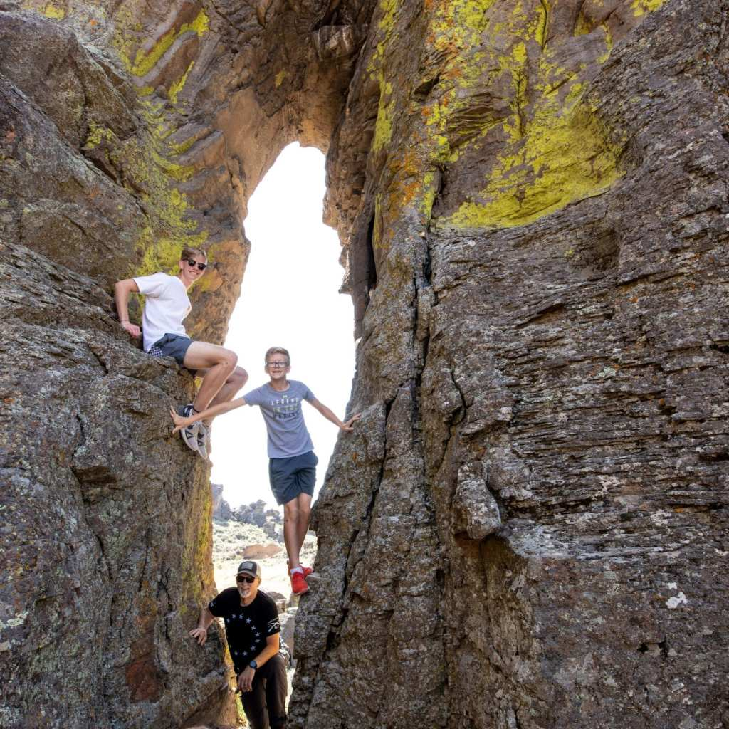 2 boys and their father climbing on hoodoos in idaho