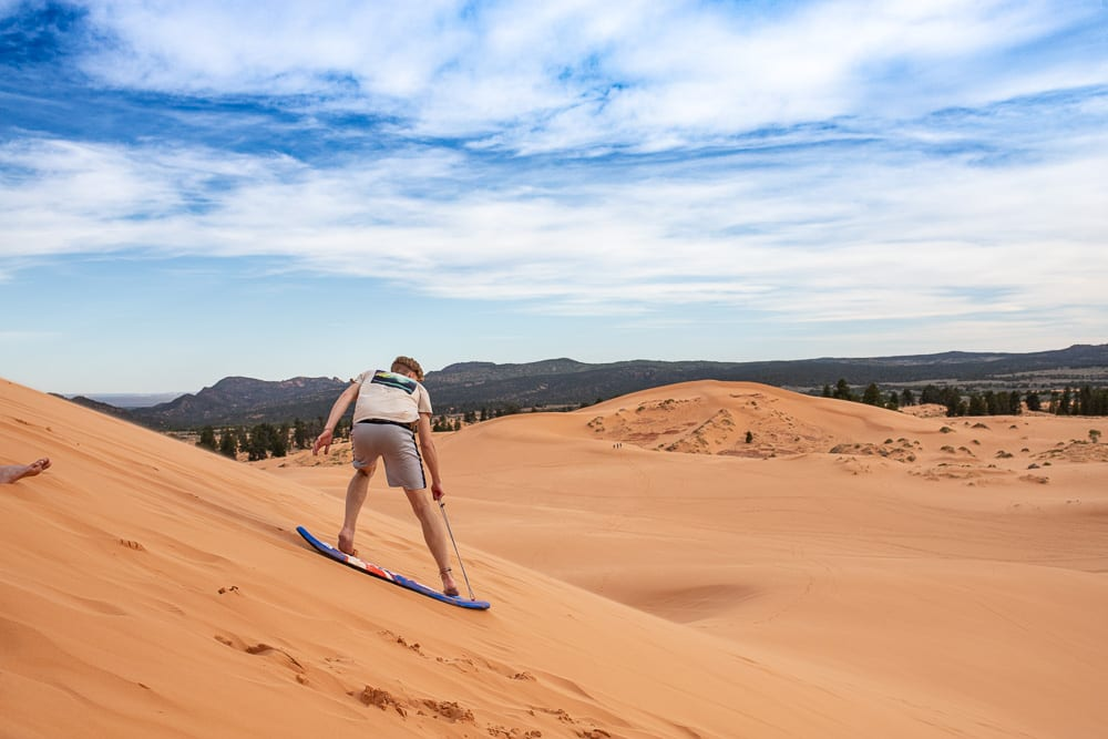 teenage boy boarding down the coral pink sand dunes