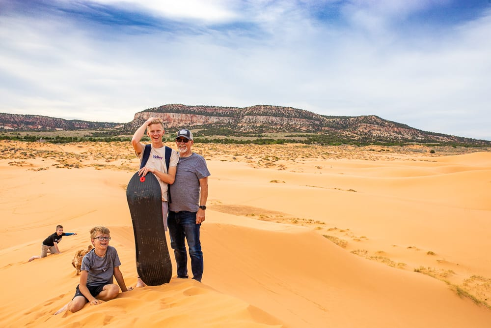 father and 2 sons standing with sled on top of coral pink sand dunes