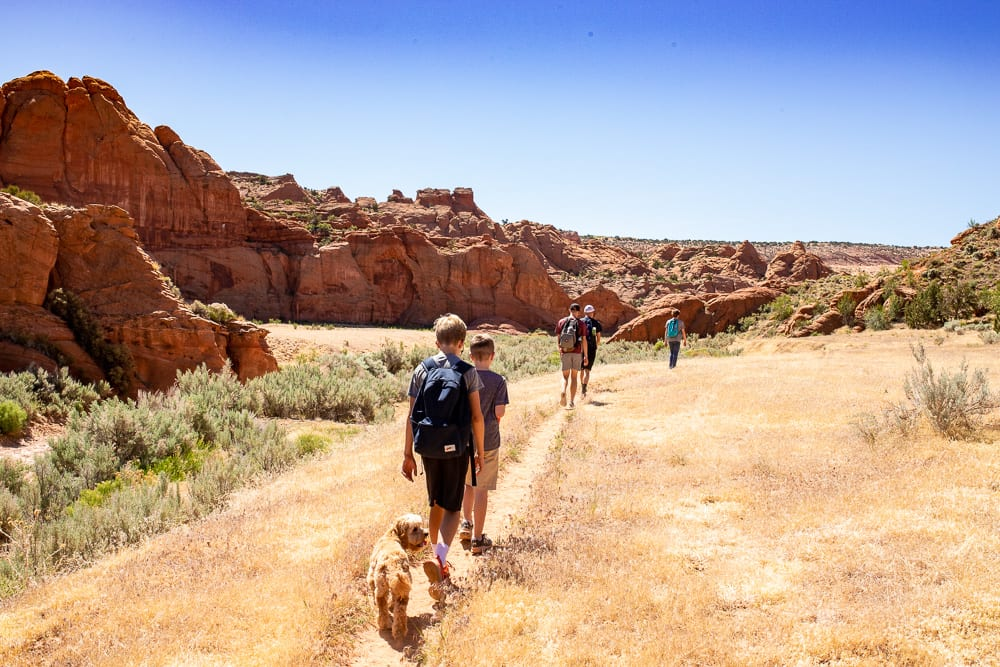 family with cavapoo walking along wire pass trail to slot canyon