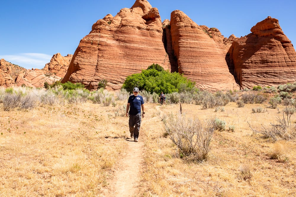 man walking on trail to slot canyons in southern utah