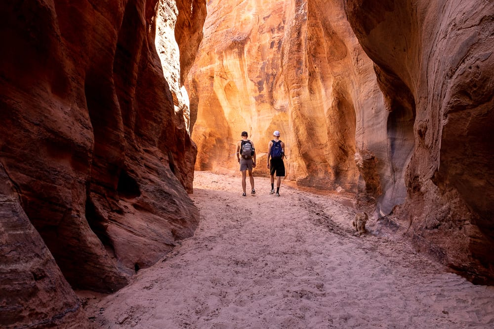 teenage boys hiking out of slot canyon in southern utah vermillion cliffs wilderness