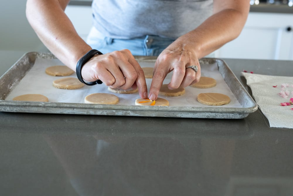 woman pressing cookie petals into shortbread cookies.