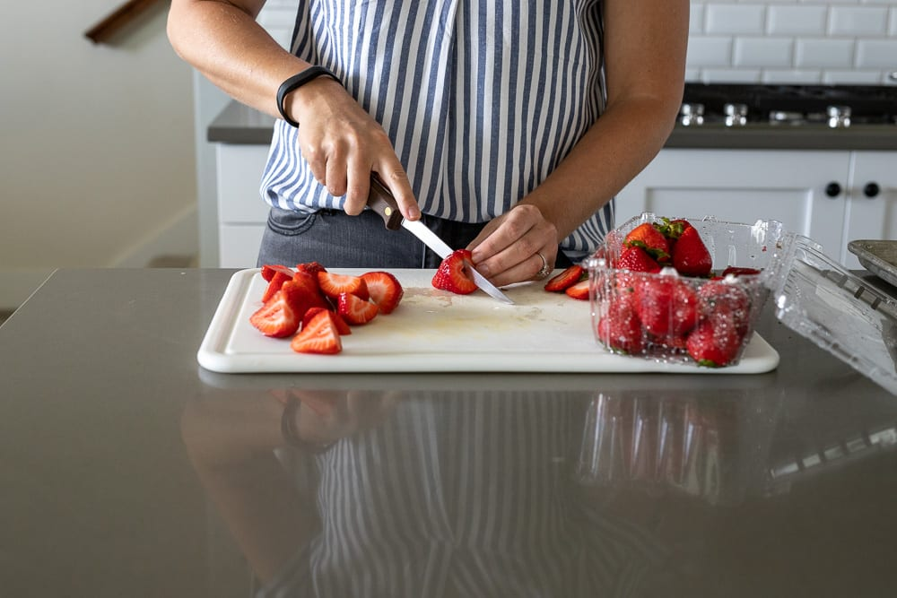 woman cutting strawberries on white plastic cutting board with knife