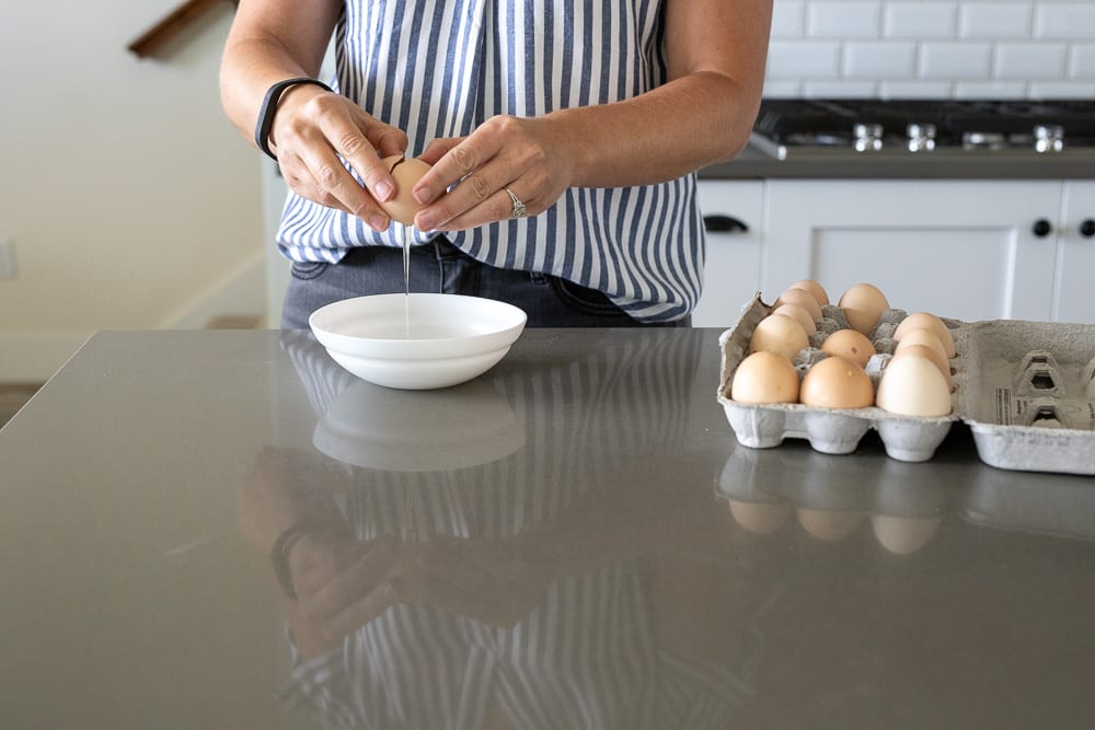 woman separating eggs into small white bowl