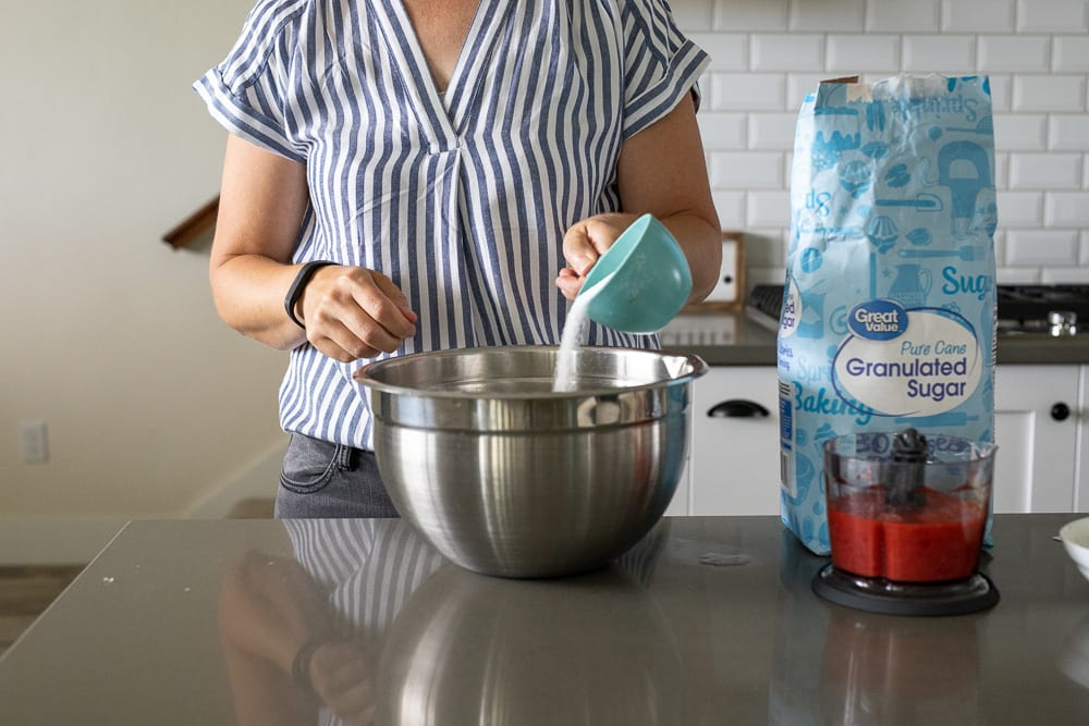 woman pouring sugar into stainless steel mixing bowl