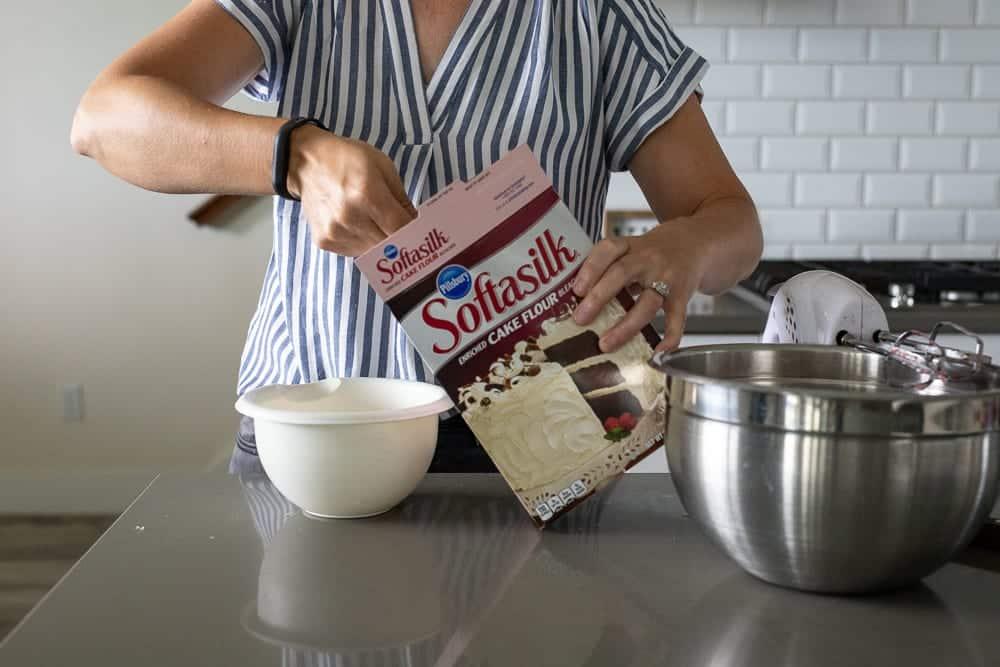 woman adding cake flour to small white plastic bowl